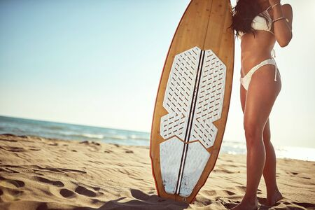 Young sexy girl posing with a surfboard on the beach. Banque d'images - 149579492