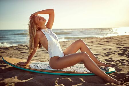 Sexy smiling woman at swimsuit on the beach.Surfer girl. Banque d'images - 149579545