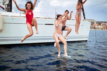 Young peoplejumping from sailboat on sea ocean trip. Stok Fotoğraf