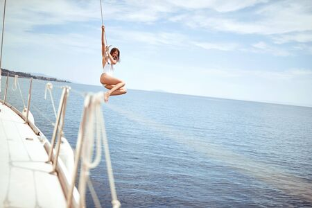 young girl hanging out, having fun and enjoying summer days jumping from sailing boat in sea. Stok Fotoğraf