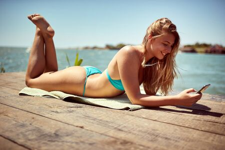 Beautiful smiling girl in  swimsuit sunbathing and texting message on mobile phone. Banque d'images - 149579660