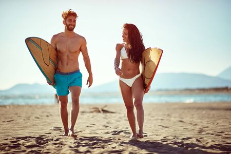 Sporty smiling people having fun going to surf together at sunset. Banque d'images - 149579670