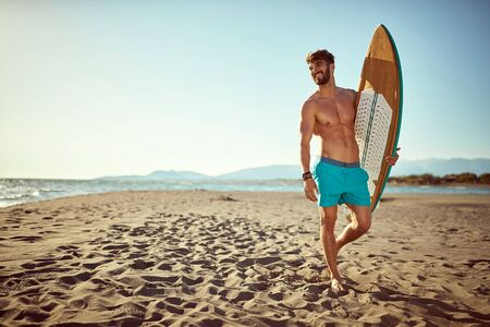 Handsome smiling man  with a surf board on the beach.