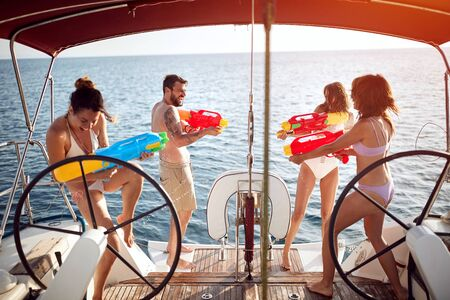 Happy young woman attack with water pistols friends man on sailing boat at vacation.