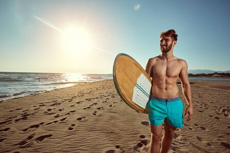 Sunny day at beach for surfing.Handsome smiling Man surfer on a beach.