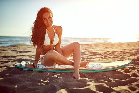 Surfer smiling girl in swimsuit bikini. Summer, holidays on the beach.