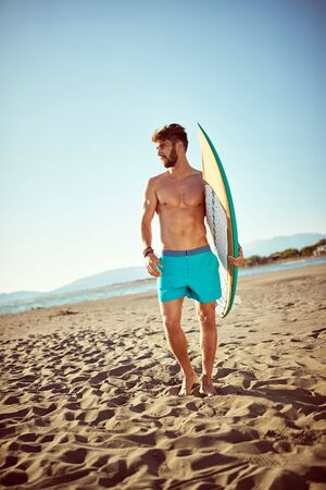 Handsome young sporty man  with a surf board on the beach. Reklamní fotografie