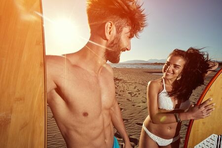 Smiling man and woman at sunny day at beach having fun and going to surf together.