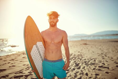 Sporty young man going to surf at vacation.