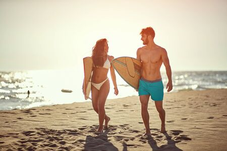 Young man and woman with a surfboard on the beach.
