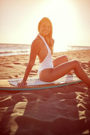 Smiling woman on the beach.  Sexy young surfer girls.