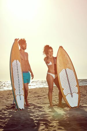 Smiling friends at sunny day at beach having fun and going to surf together. Reklamní fotografie