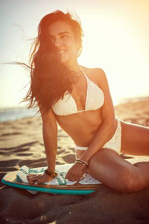 Surfer smiling woman in swimsuit bikini. Summer, holidays on the beach.