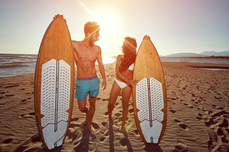 Smiling couple at sunny day at beach having fun and going to surf together.