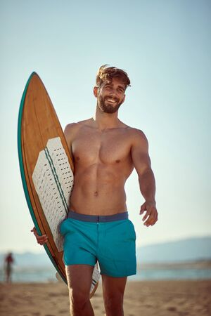 Young smiling man going to surfing on the beach.Man with  surfboard at summer.