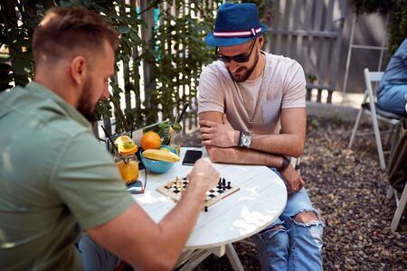 Friends are playing the chess in relaxed atmosphere of cafe's garden Stock Photo