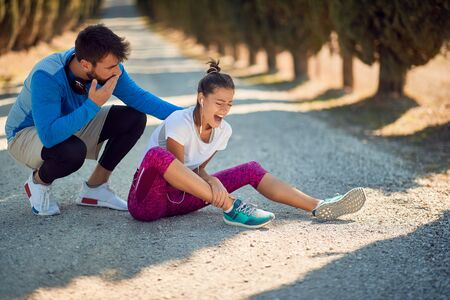 worried male with a hand on his mouth encouraging young female with sport injure