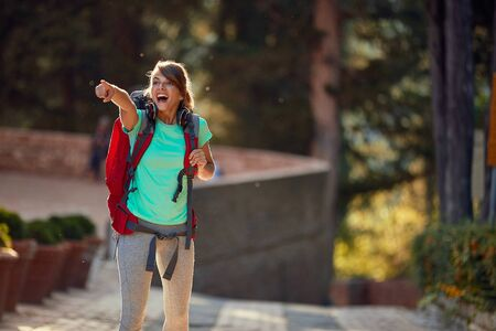 young female delighted by sightseeing in italy, showing thrilled with index finger what she saw Imagens