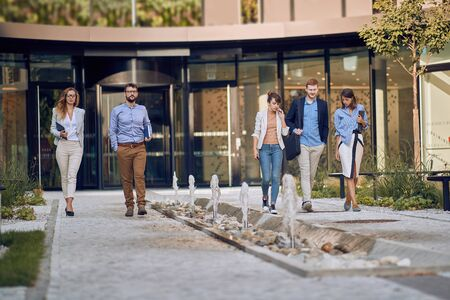 group of caucasian business people walking and talking in front of business building