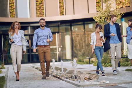 caucasian business partners walking and talking in front of business building
