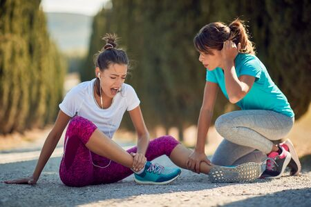 worried female comfort other one with injured ankle. sport injury Banque d'images