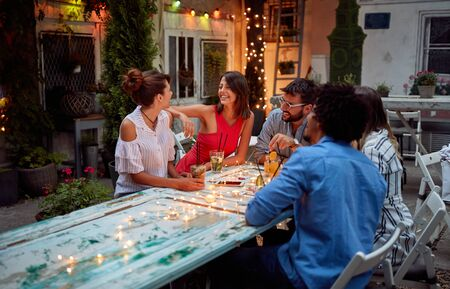 Young friends enjoy friendly conversation at dusk at cafe's garden Stockfoto