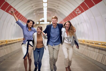 young people hugged walking through public underground pedestrian tunnel, smiling, laughing, celebrating