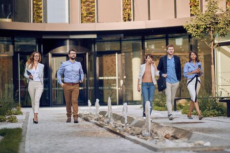 caucasian businesspeople walking and talking in front of business building