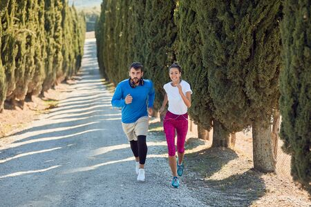young caucasian female jogging uphill with personal trainer on a gravel road . car with sport equipment following them. professional, personal, trainer Banque d'images