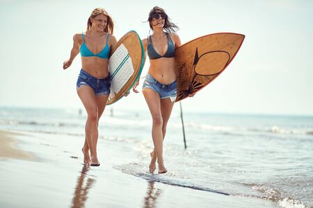 Happy womans with  surfboard walking at beach.Sexy girls with  surfboard at summer.