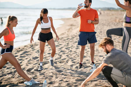group of young caucasian adults doing exercises on sandy beach. beardy guy drinking water from a plastic bottle