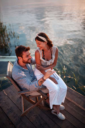 top view of a beautiful woman sitting in a lap of a man by the water, talking, smiling. copy space