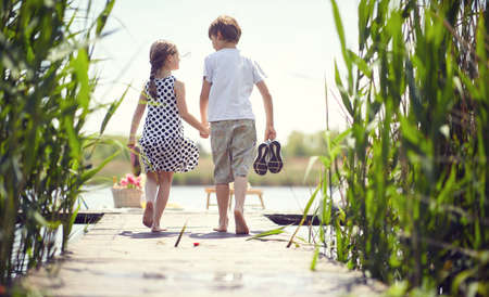 Little boy and girl near pond.Kids during  goes on the pond.  Banque d'images