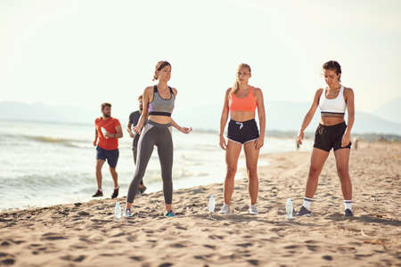 group of three women preparing to exercise on a sandy beach while two men jogging in the background