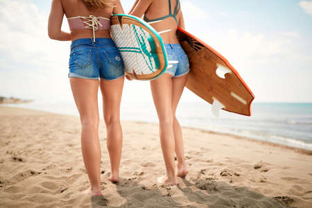 Seductive female surfers in hot short pants on a beach Stock fotó