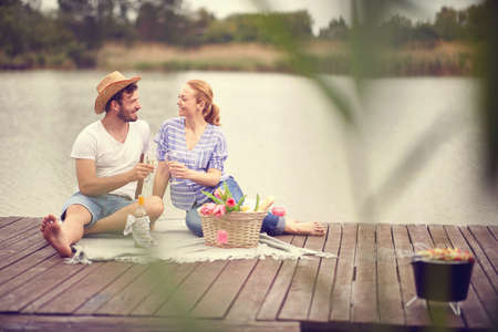 Young smiling couple enjoying at wine.Romantic picnic on lake.