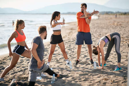 caucasian group of two men and three women stretching, warming up for exercising at the beach
