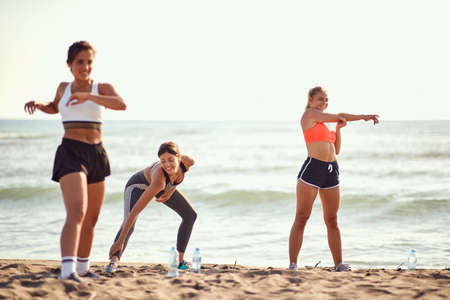 caucasian women exercise, stretching and warming up on a sandy beach
