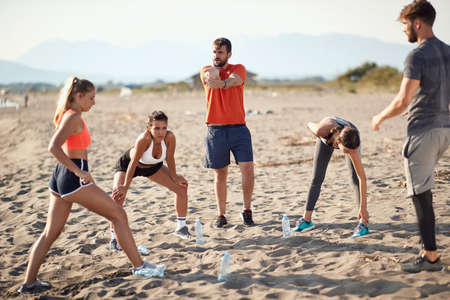 caucasian group of two men and three women stretching, warming up for exercising at sandy  beach