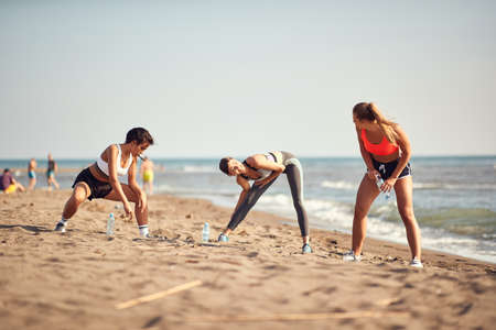 caucasian women exercise, stretching and warming up on a beach