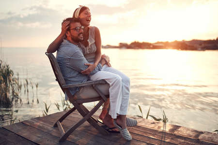 beautiful woman sitting in a lap of a man at sunset, laughing