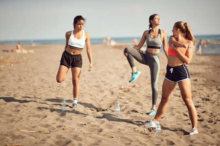 three caucasian women exercise, stretching and warming up on a sandy beach Imagens