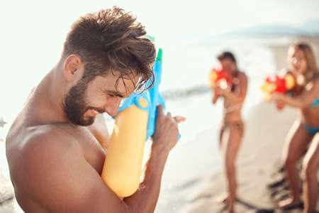 two women sprinkle beardy guy with water guns Standard-Bild