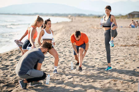 group of young caucasian men and women stretching, warming up for exercising at the beach Imagens
