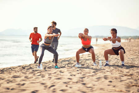 group of three women exercise on a sandy beach while two men passing by, jogging