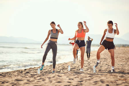 group of three women exercise on a sandy beach with two men walking in the background