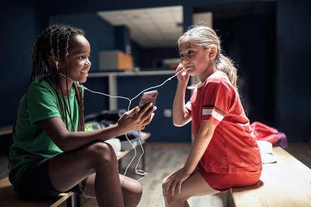 Two smiling girl soccer player before training listen music on phone in locker room.