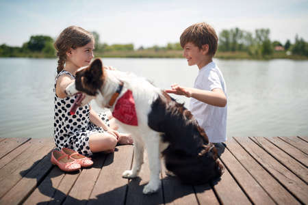 cute caucasian boy and girl sitting by the river, smiling, talking, cuddling the dog