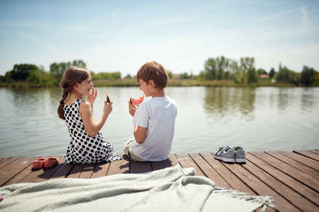 minor caucasian couple sitting by the river eating watermelon