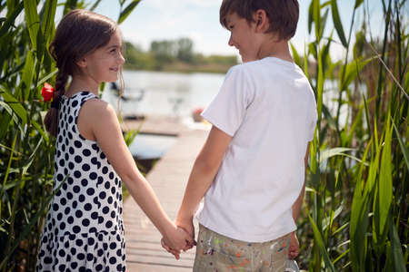 close up image of caucasian boy and girl holding hands, walking toward the water , smiling